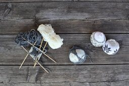 Knitting needles stuck in ball of wool and knitted baubles with Norwegian patterns on weathered wooden surface