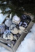 Grey and white knitted baubles with Norwegian patterns in weathered wooden crate and fir branches in snow