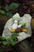 Crocheted toadstools lying on cloth in woodland