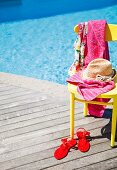Straw hat and pink towel on yellow chair and red ladies' sandals on sunny wooden terrace next to pool
