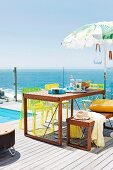 Wooden table, matching bench and yellow chairs on sunny wooden terrace beside pool with sea view through glass balustrade