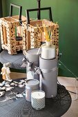 Festive arrangement of candles, presents wrapped in grey and wooden lanterns