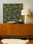 Panel of floral fabric, table lamps and books on fifties sideboard