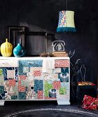 Colourful sideboard with patchwork motifs in front of wall painted with blackboard paint