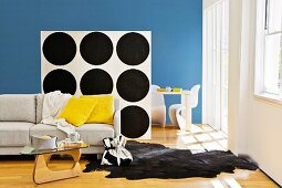 Seating area with sofa, animal-skin rug & coffee table separated by partition shelving with back wallpapered in black and white pattern of circles