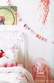 Ausschnitt eines weissen Metall Gitterbetts, daneben Kinderstuhl aus eingefärbtem, transparentem Kunststoff, an Wand Girlande und und Deko Tierfigur