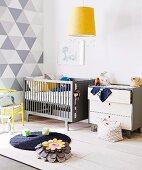 Hellgraue Kommode und Gitterbett an Wand mit geometrischem Muster in Weiss und Grau, vorne Hängeleuchte mit gelbem Schirm über dekoriertem Boden