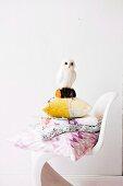 weiße Eulenfigur auf Kissenstapel und weißem Kunststoff Schalenstuhl