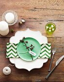Green and white zig-zag napkin on plate with ornate rim, lime green desert plate and candles arranged on rustic wooden table