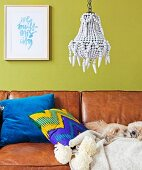 Dog sleeping on comfortable leather sofa with scatter cushions against lime green wall below pendant lamp decorated with white beads