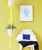 Green plant in yellow macrame plant hanger next to stack of cushions on chair against lime green wall