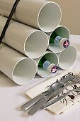 DIY wine rack made from tied bundle of white plastic tubes