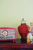 Fifties-style radio next to red paper lantern with black metal frame against pastel green wall