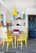 Yellow pendant lamp above round oak table and yellow-painted Thonet chairs on black and white striped rug in front of open-plan kitchen with drawings on blackboard to one side