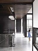 Long corridor in minimalist house with dark grey wall elements and window frames, stone-clad island counter and bar stools in kitchen