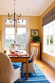 Wooden table with elegant wicker chairs on blue and white carpet in the dining area with yellow walls