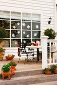 Terrace in front of a Christmas decorated window of a white wooden house