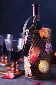 Wine bottle holder decorated with colourful, painted autumn leaves