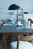 Blackboard table set with punchbowl and cups under black pendant lamp