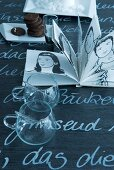 Glass cups and book of black and white drawings on blackboard tabletop with white lettering