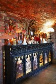 Console cabinet with backlit religious panels and hotchpotch of ornaments on top against brick wall