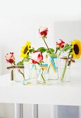 Single sunflowers and roses in glass vases decorated with ribbon