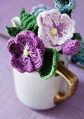 Purple crocheted flowers arranged in nostalgic milk jug