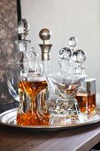 Crystal carafes with spherical stoppers on silver tray