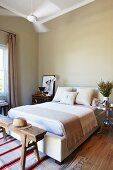 Double bed with blanket and stacked scatter cushions against grey-painted wall with rustic wooden bench at foot of bed