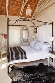 Four-poster bed with striped brown blanket and exposed roof structure with bamboo covering