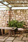 Vintage garden chair with cushion and rustic wooden bench on stone floor of terrace with bamboo pergola and tall stone wall