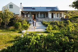 Woman walking down gravel path in summery garden; country house with stone base in background