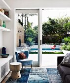 Blue retro armchair next to white built-in shelves and garden view with pool