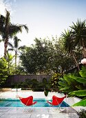 Pool with two red butterfly chairs behind glass balustrade