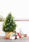 Kieferbäumchen mit Holzbuchstaben und herzförmigen Anhängern im Strohkorb, daneben Weihnachtsgeschenke und Spielzeuge