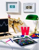 Desk in a child's room decorated with a chalkboard shaped like a laptop, piggy bank and calculator shaped like an iPad