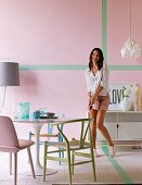 Various pastel chairs around Tulip Table and woman in front of pink wall with green stripes