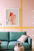 Petrol-blue sofa below picture of bird on pink wall with yellow stripes