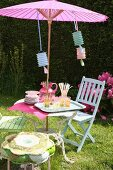 Glasses and carafe on garden table with Oriental parasol and party decorations