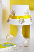 Flower-shapes cut from map and golden ribbon decorating lampshade