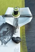 Sushi roll on designer plate on paper place mat with drawing of fish and green runner