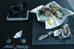 Minimalist table arrangement in charcoal - iced oysters in crumpled-effect dish on table top painted with blackboard paint