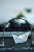 Paper boat with name seen through stylised bridge on dark table top