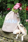 Hand-sewn, polka dot sports bag with sewn-on name next to ballet shoes on stone wall in garden