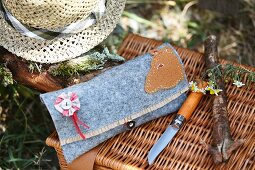 Grey felt pouch with hand-sewn appliqué motifs on picnic basket