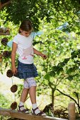 Child wearing hand-sewn T-shirt balancing on wooden beam in garden