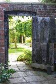 Open wooden door in brick wall showing row of trees in English garden