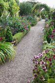 Blooming flower beds lining long gravel path leading through climber covered arch in English garden