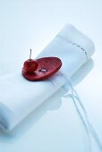 Oriental table decoration; white linen napkin with large, red button and cord as napkin ring