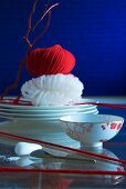 Oriental table setting: bowls amongst red woollen yarn, glass noodles on stacked plates and ball of red yarn